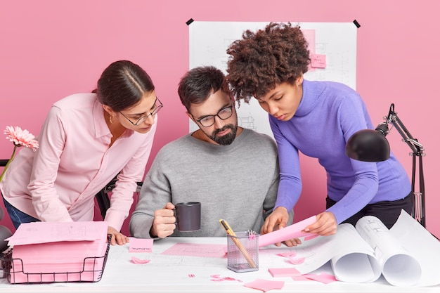 Trzech różnych współpracowników współpracuje i odbywa burzę mózgów, uważnie przygląda się dokumentom, pozuje na biurku ze szkicami, omawia pomysły dotyczące strategii produkcyjnej, spotyka się w biurze firmy