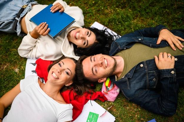 Trzech studentów, leżąc na trawie i uśmiechając się