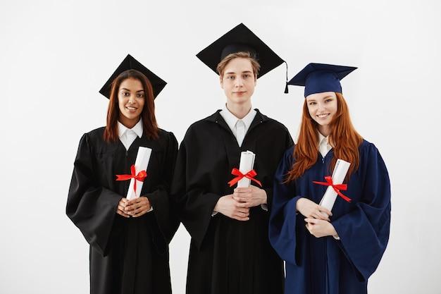 Trzech szczęśliwych absolwentów uśmiecha się gospodarstwa dyplomy.