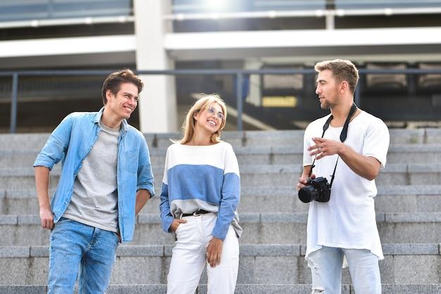 Trzech szczęśliwych przyjaciół rozmawia w słoneczny dzień na ulicy z budynkami w backgro