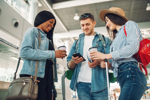 Trzech turystów z bagażem czeka na odlot i pije kawę na lotnisku, podróżujący mężczyzna korzystający z telefonu komórkowego.