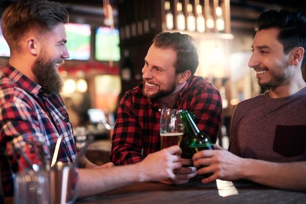 Trzech uśmiechniętych mężczyzn pijących piwo w pubie