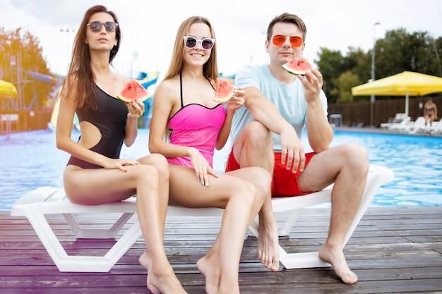 Trzech uśmiechniętych przyjaciół z kawałkami arbuza. zabawa na basenie w towarzystwie znajomych. letnia impreza na plaży. miejski aquapark. wakacje.