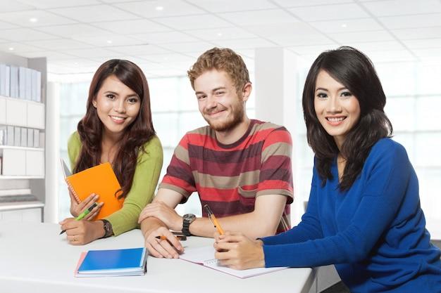 Trzech uśmiechniętych studentów studiujących razem
