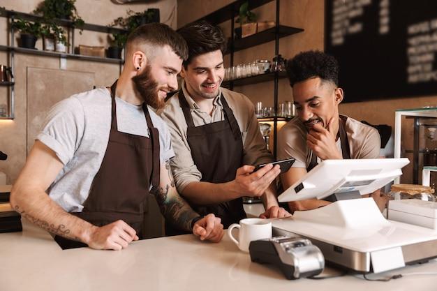 Trzech wesołych baristów stojących za ladą w kawiarni, korzystających z telefonu komórkowego