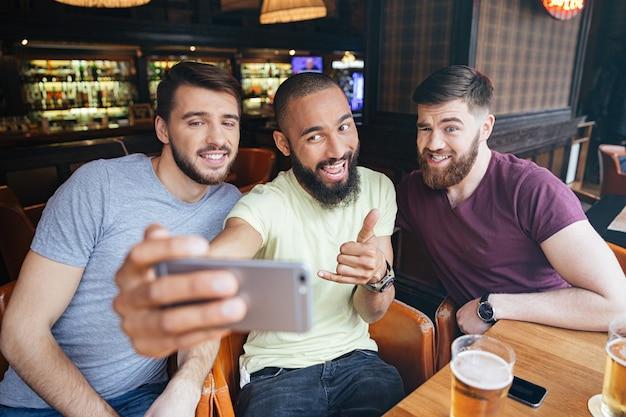 Trzech wesołych przyjaciół robi zdjęcie selfie na smartfonie w pubie piwnym