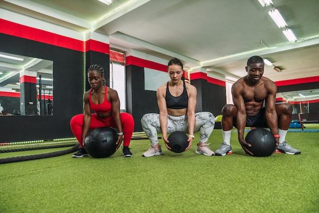 Trzech wielorasowych atletów kulturystów robi tonujące ćwiczenia z piłką na siłowni. dwóch afrykańskich kulturystów i kulturysta rasy kaukaskiej podczas treningu crossfit.