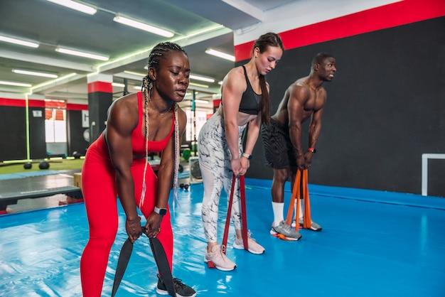 Trzech wielorasowych atletów kulturystów wykonujących ćwiczenia wzmacniające z elastycznymi taśmami na siłowni tułowia. dwóch afrykańskich kulturystów i kulturysta rasy kaukaskiej podczas treningu crossfit