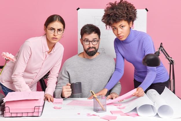 Trzech wielorasowych inżynierów analizuje szkic i rozmawia ze sobą poważnie, pracując nad projektem architektonicznym we współczesnej pozie biurowej na pulpicie. doświadczeni pracownicy sprawdzają szkic młodego pracownika