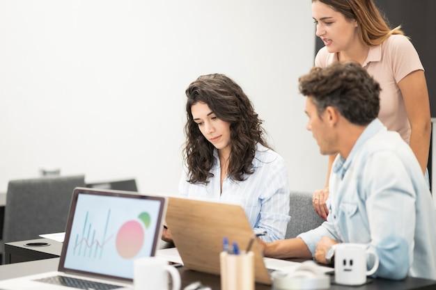 Trzech współpracowników w biurze, prezentujących nowy projekt