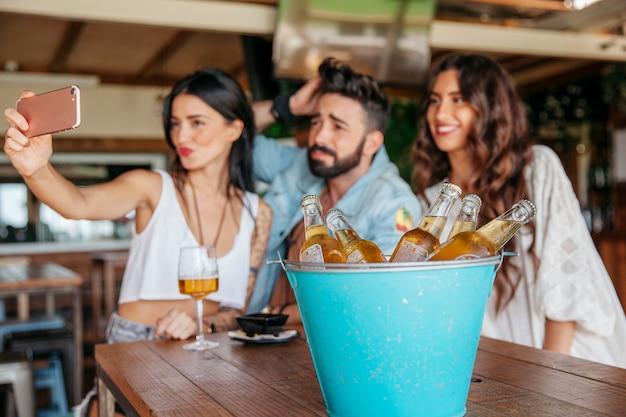 Trzech znajomych stwarzających dla selfie w barze