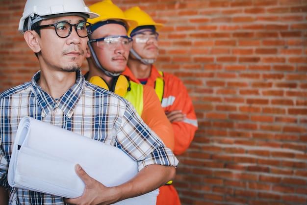 Trzej azjatyccy inżynierowie lub architekci z pomysłem pracy jako zespół budowlany - nadzór i zwolennicy stoją na placu budowy