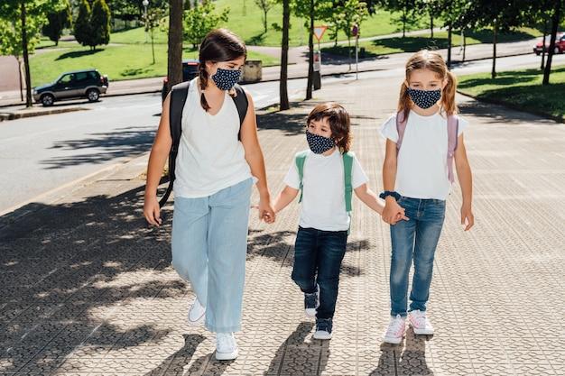 Trzej kaukascy bracia w różnym wieku idą do szkoły na początku roku z maskami na twarzach z powodu pandemii koronawirusa covid19