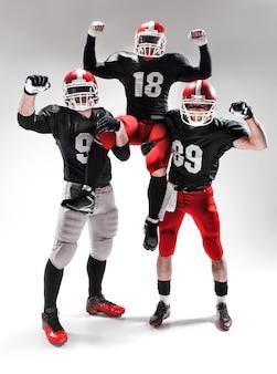 Trzej kaukascy fitness mężczyźni jako zawodnicy futbolu amerykańskiego udający zwycięzców na biało i radośnie