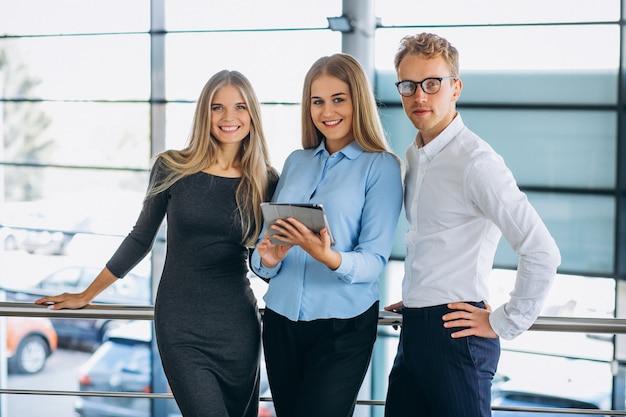 Trzej koledzy pracujący w salonie samochodowym