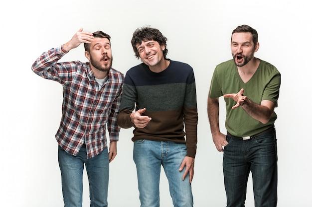Trzej młodzi mężczyźni uśmiechają się, stojąc na bieli z różnymi emocjami