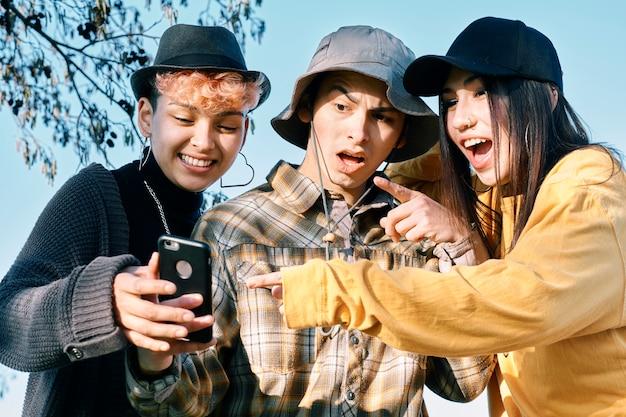 Trzej młodzi przyjaciele, którzy noszą różne rodzaje kapeluszy, patrzą na swoje telefony komórkowe w szoku i zdziwieniu