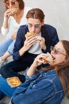 Trzej przyjaciele jedzą hamburgery na świeżym powietrzu