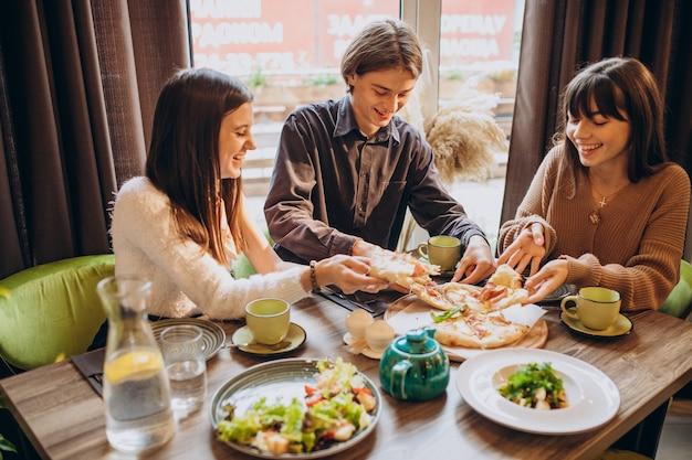 Trzej przyjaciele razem jedzą pizzę w kawiarni