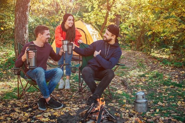 Trzej przyjaciele są razem w lesie. trzymają kubki razem i patrzą na siebie. niektóre z nich trzymają termosy w rękach. oni są szczęśliwi.