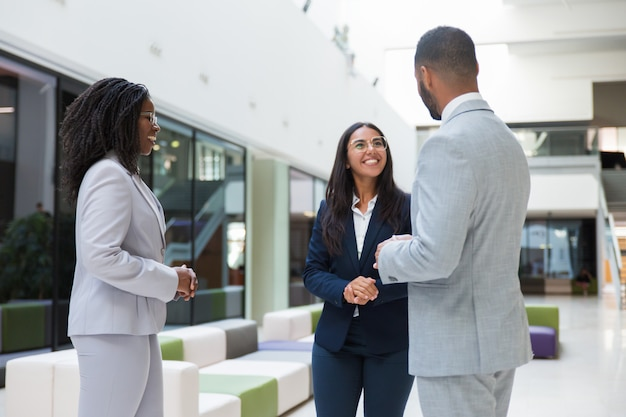 Trzej różnorodni partnerzy biznesowi spotykają się w hali biurowej