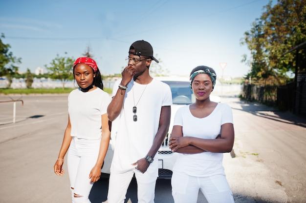 Trzej stylowi przyjaciele z afryki, noszą białe ubrania na tle dwóch luksusowych samochodów. moda uliczna młodych czarnych ludzi. murzyn z dwoma afrykańskimi dziewczynami.