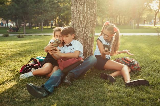 Trzej szkolni przyjaciele siedzą na trawie pod drzewem i grają w swoje gadżety. przyjaciele nie komunikują się w życiu, preferując telefon