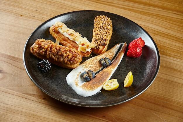 Trzy apetyczny i duży ekler z polewą na wierzchu i kremem jodłowym w środku na czarnym talerzu