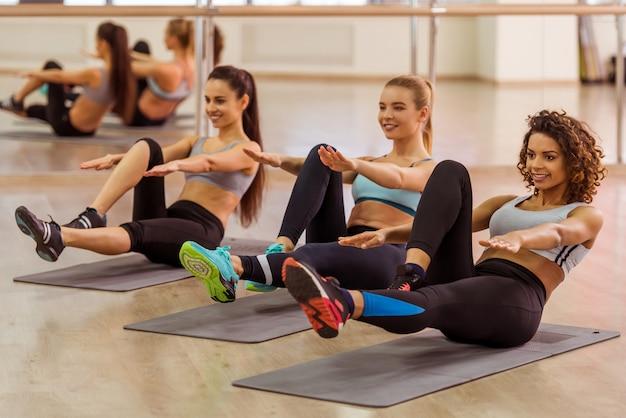 Trzy atrakcyjne dziewczyny sportowe uśmiecha się podczas wykonywania abs.
