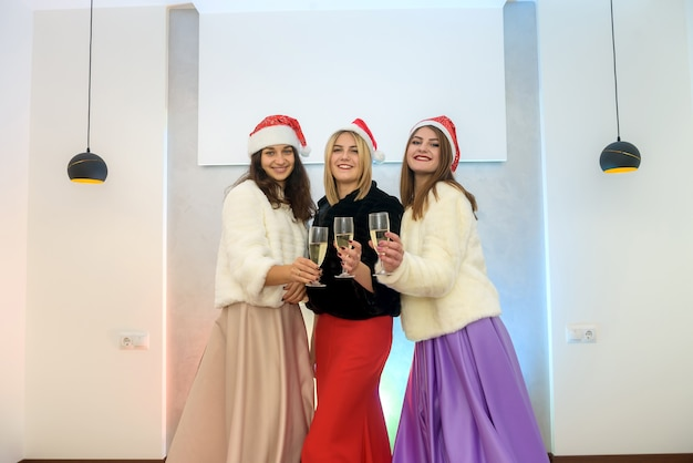 Trzy atrakcyjne kobiety z kieliszkami do szampana wznoszą toast na przyjęciu. obchody nowego roku