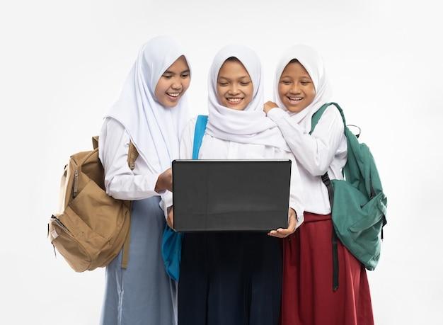 Trzy azjatki w welonach w szkolnych mundurkach stoją razem uśmiechając się przy laptopie, niosąc...