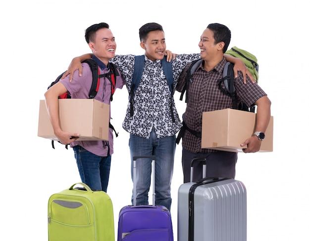 Trzy azjatykcia męska idzie urlopowa mienie walizka