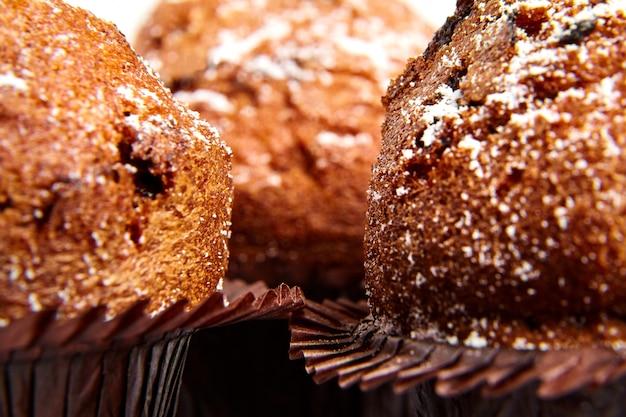 Trzy babeczki z kawałkami czekolady i cukrem pudrem