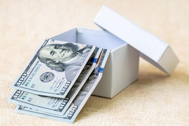Trzy banknoty dolar amerykański 100 dolarów w białym pudełku. strzał studio.