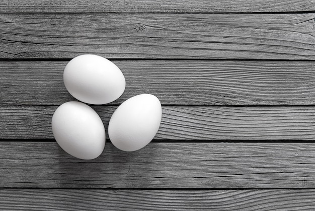 Trzy białe jajka na szarym drewnie