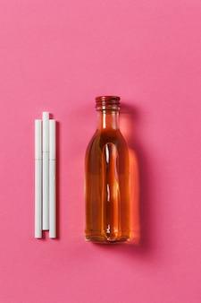 Trzy białe papierosy, butelka z alkoholem koniak, whisky na różowym tle róży