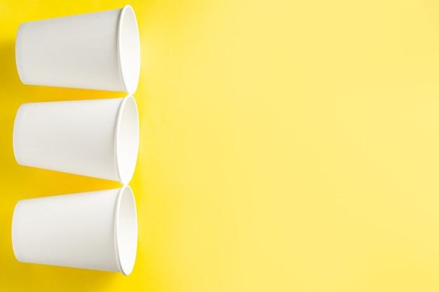 Trzy białe papierowe filiżanki kawy na żółtym tle. miejsce dla tekstu. widok z góry.