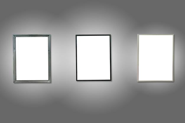 Trzy białe pojedyncze drewniane ramki na szarej ścianie