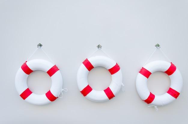 Trzy biały czerwony lifebuoy z deską na biel ścianie