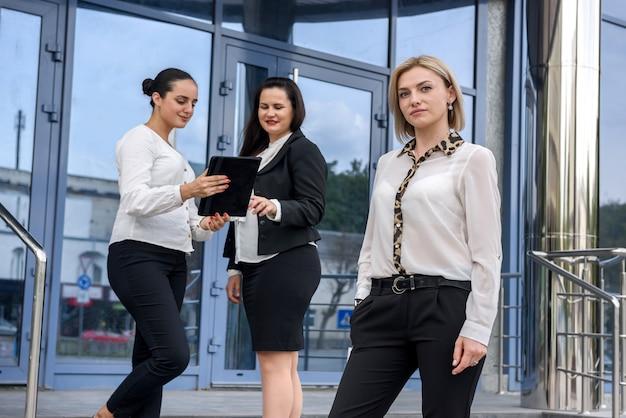 Trzy biznesowe panie z tabletami stoją na zewnątrz budynku i patrzą w kamerę