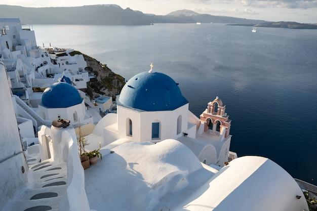 Trzy błękitnej kopuły santorini oia kościelna wioska w santorini wyspie, grecja.
