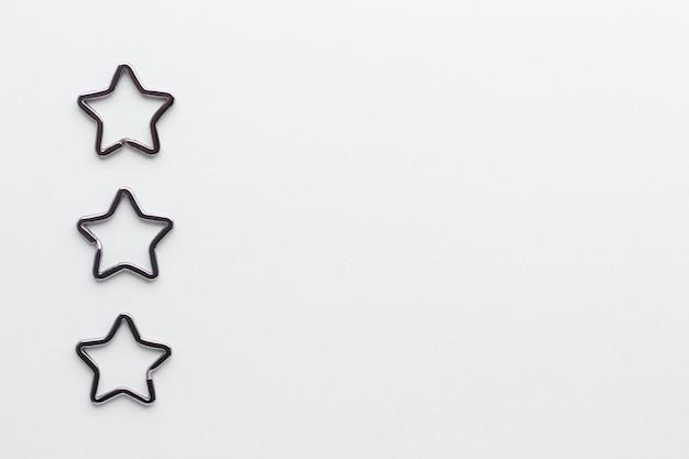 Trzy błyszczące metalowe kółka na klucze w kształcie gwiazdy do breloków. chromowane zapięcie na brelok na białym tle.