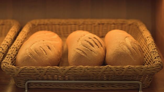 Trzy bochenki chleba pszennego w koszu. piekarnia