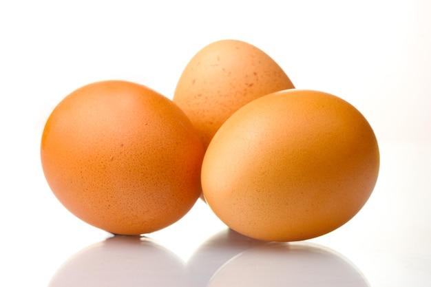 Trzy brązowe jajka na białym tle
