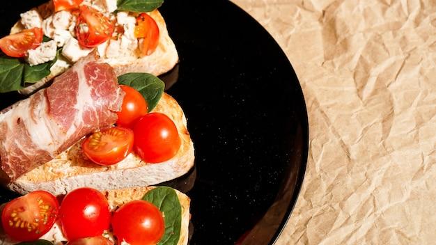 Trzy bruschetta na czarnym talerzu na papierze rzemieślniczym. przystawka z pomidorkami koktajlowymi, twarogiem, szpinakiem i boczkiem.