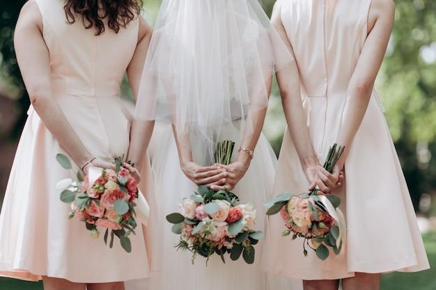Trzy bukiety ślubne trzymane przez pannę młodą i jej druhny