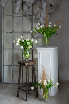 Trzy bukiety tulipanów w wazonach we wnętrzu