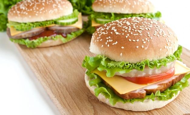 Trzy burger z mięsem i warzywami na talerzu drewna
