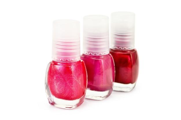 Trzy butelki lakieru do paznokci z różnymi odcieniami koloru czerwonego na białym tle