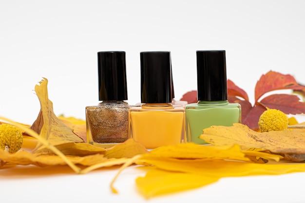 Trzy butelki lakieru do paznokci z żółtymi jesiennymi liśćmi.